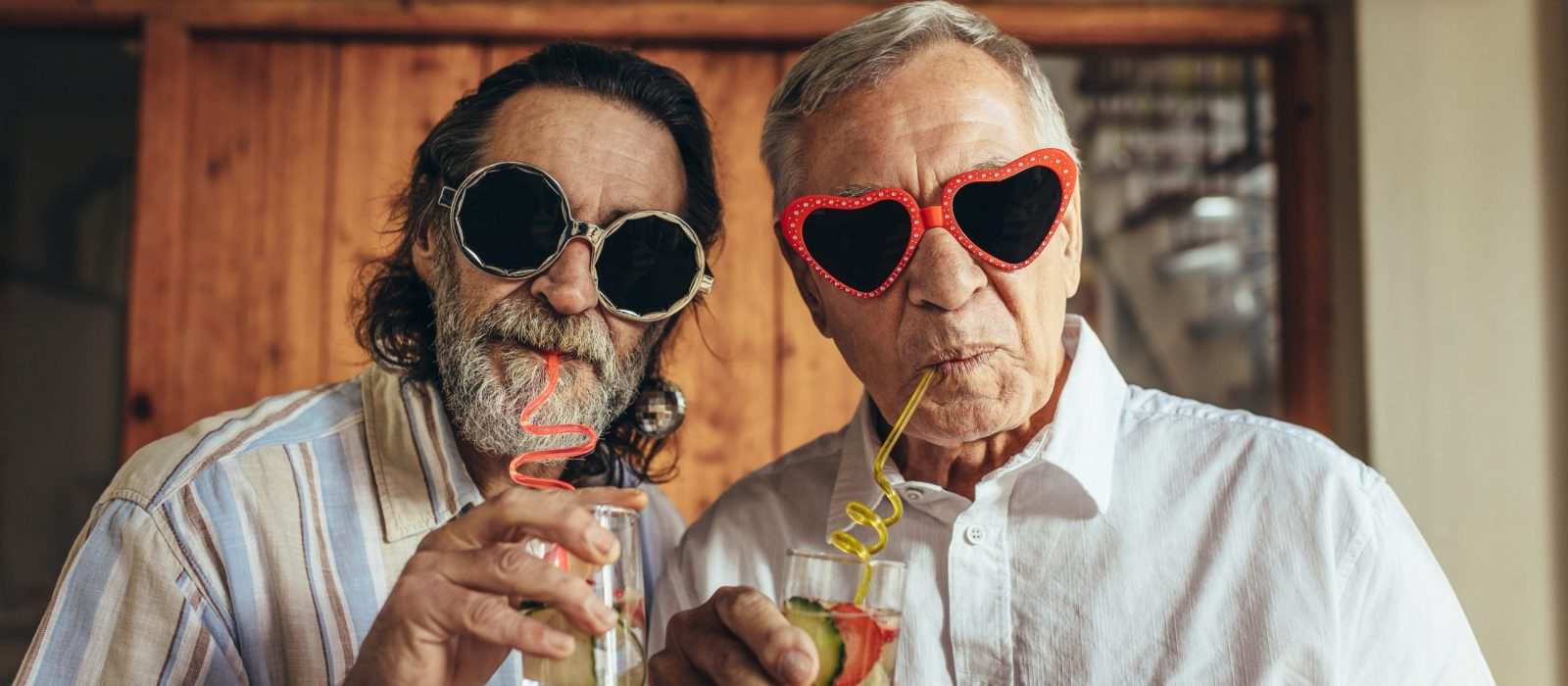 Senior men wearing funny sunglasses drinking juice with straw. Elderly friends with crazy eyewear having juice indoors.